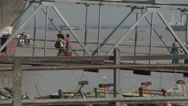 Stock Video Footage of ASIAN PORT & JETTY:  BURMA - Workers carry sacks along gangway with port behind