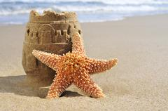 starfish and sandcastle on the beach - stock photo
