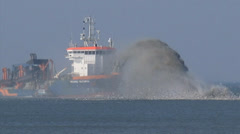Trailing suction hopper dredger rainbowing at North Sea coast zoom out/in Stock Footage