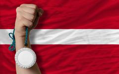 silver medal for sport and  national flag of latvia - stock photo