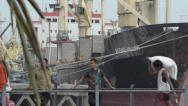 Stock Video Footage of ASIAN PORT & JETTY:  BURMA - Worker carries large sack past a large ship