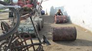 Stock Video Footage of ASIAN PORT & JETTY:  BURMA - Worker rolls oil barrel towards camera