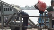 Stock Video Footage of ASIAN PORT & JETTY:  BURMA - Porter carries sack and worker rolls oil barrel
