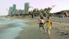 Little Kids Chase A Flock Of Seagulls, Then Run Down The Beach Toward Camera Stock Footage