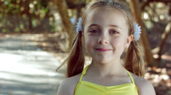 Cute Little Girl Smiles At Camera, Looks Over Her Shoulder, Back To Camera Stock Footage