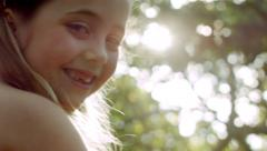Little Girl Sits In Tree, Smiles Over Her Shoulder At Camera Stock Footage