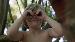 Curious Little Boy Sits In Tree And Looks Through His Pretend Binoculars Stock Footage