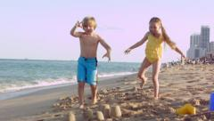 Little Kids Pretend To Be Monsters Or Giants, And Crush Their Sand Castle City Stock Footage