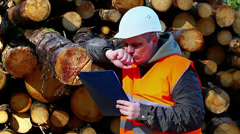 Forest employee with folder near logs Stock Footage
