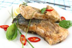 fried fish on white plate, fork and knife - stock photo
