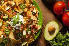Homemade unhealthy nachos with cheese and vegetables Stock Photos