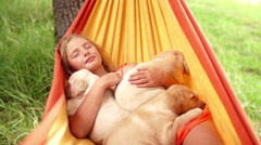 Girl sleeping with puppies in hammock Stock Footage