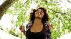 African american young woman on a swing slow motion Stock Footage
