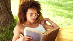 Young african american woman reading book in a hammock Stock Footage