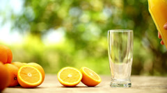 Pouring fresh orange juice into glass on breakfast table Stock Footage