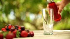 A person pouring berry fruit juice in glass in slow motion Stock Footage