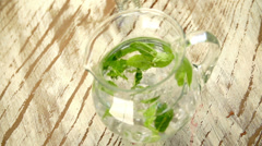 Jug of water with fresh mint leaves - stock footage
