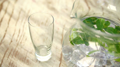 Fresh mint water pouring from pitcher into glass in slow motion - stock footage