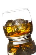 alcoholic whiskey bourbon in a glass with ice - stock photo