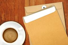 Brown envelope document and a white coffee cup on a wooden desk Stock Photos