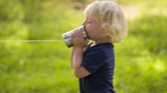 Boy using a string can phone Stock Footage