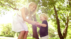 Mom and son dancing in park Stock Footage