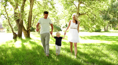 Parents swinging boy holding hands Stock Footage