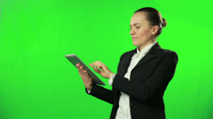Young businesswoman working on tablet computer against a green screen HD - stock footage