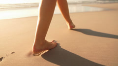 Woman leaving footbrints in sand - stock footage