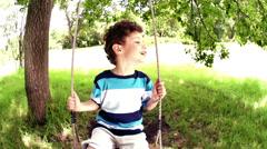 Boy on swing in park Stock Footage
