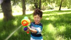 Boy playing with squirt gun Stock Footage