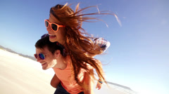 Couple piggyback on beach Stock Footage