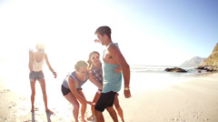Girls lifting friend on beach Stock Footage