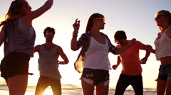 Friends dancing on beach in sunset Stock Footage