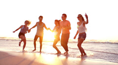 Friends dancing on beach in sunset - stock footage