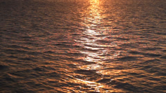 Beautiful sunset reflection sparkles on tiny ripples of sea water - stock footage