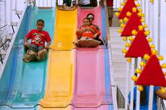 family slides down fun slide at atlanta fair - stock photo