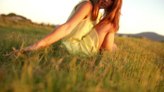 Girl is sitting in grass while sunset - stock footage