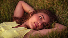 Girl lying in grass at sunset Stock Footage