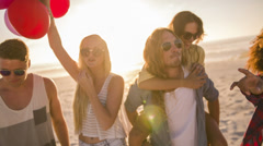 Friends dancing with balloons on beach Stock Footage