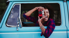 Girl with retro camera in old car Stock Footage