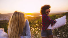 Friends having Pillow fight at sunset Stock Footage