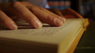 Stock Video Footage of Hand over book while reading. Close Up.