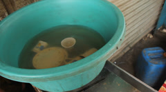 Cups and Teapots Being Rinsed in a Basin of Murky Water Stock Footage