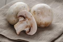 Fresh white champignon on wood table Stock Photos