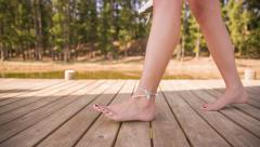 girl walking barefoot on jetty - stock footage