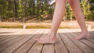 Girl walking barefoot on jetty Stock Footage