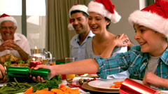 Siblings pulling a christmas cracker at the dinner table - stock footage