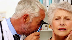 Doctor examining his patients ears - stock footage