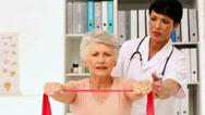 Stock Video Footage of Nurse showing elderly patient how to use resistance band
